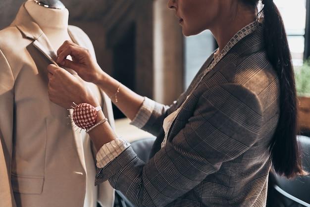 Ее дизайн идеален. крупным планом молодой женщины, шить куртку на манекен, стоя в своей мастерской