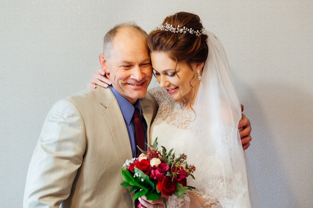 Her father hugs her daughter to the bride who holds a wedding bouquet in her hands