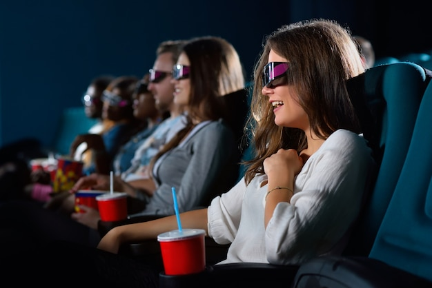 彼女の新しいお気に入りのコメディ。映画館でコメディ映画を楽しみながら笑っている陽気な若い女性のトリミングされたクローズアップショット