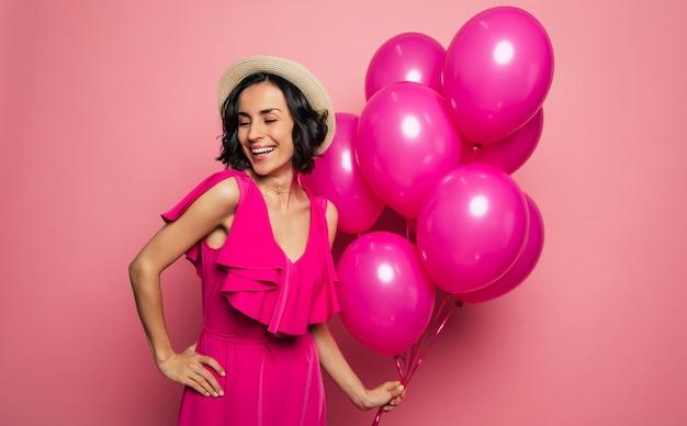 Ее идеальный день рождения. молодая очаровательная женщина в платье цвета фуксии и соломенной шляпе держит розовые воздушные шары в левой руке и смеется.