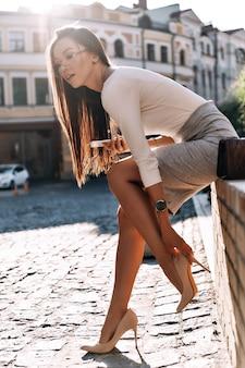 그녀의 신발은 그녀에게 문제를 줍니다. 야외에 앉아 있는 동안 신발을 조정하고 눈을 감고 있는 매력적인 젊은 여성