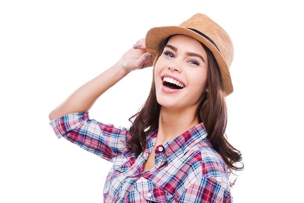 그녀의 미소가 무너지고 있습니다. 펑키한 옷을 입은 아름다운 젊은 여성이 모자를 조정하고 흰색 배경에 서서 카메라를 보며 웃고 있습니다