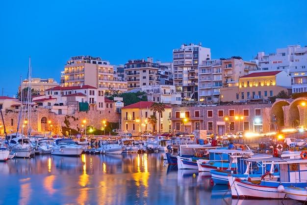 해질녘에 요트와 어선이 있는 항구가 있는 헤라클리온 도시, 그리스 크레타 섬