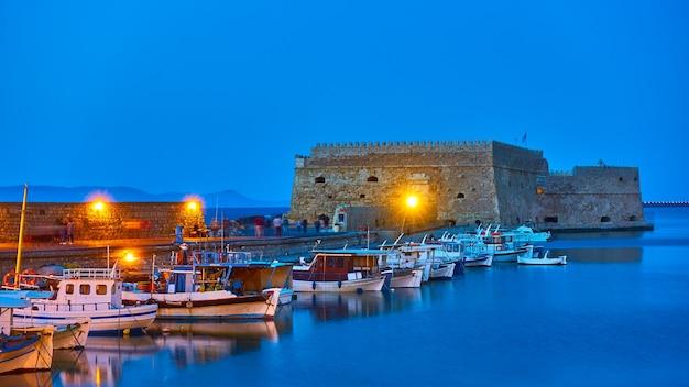 그리스 크레타 섬의 이라클리온. 황혼에 오래된 베네치아 요새 옆에 어선이 있는 항구