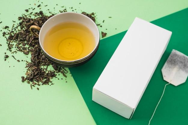 Травяная коробка с чашкой чая на светлом и темном фоне