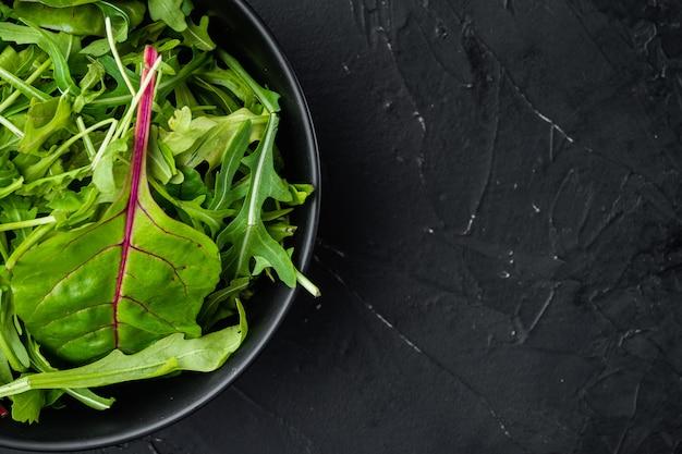 Зеленый салат из зелени с рукколой и мангольдом, швейцарский мангольд, на черном каменном фоне, плоская планировка, вид сверху, с местом для текста