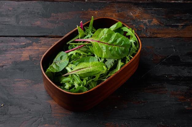 Зеленый салат с рукколой и мангольдом, швейцарский мангольд, на фоне старого темного деревянного стола