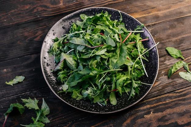 ルッコラ、ほうれん草、フダンソウのハーブグリーンサラダ。ベジタリアンヘルスサラダ。上面図