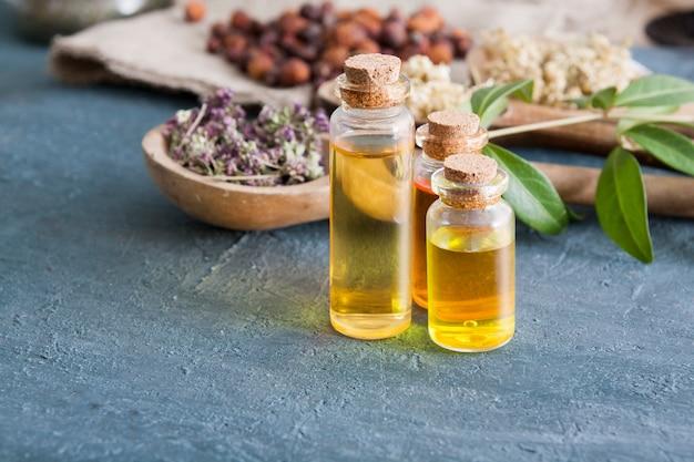 Настойки трав в стеклянных бутылках на темном бетонном столе. традиционная медицина и концепция лечения травами.