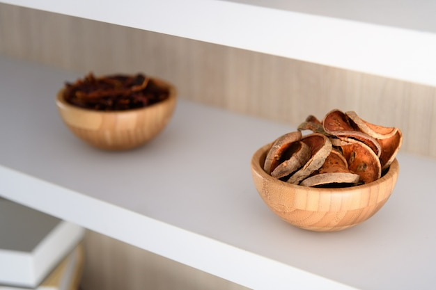 Herb in wood bowl on shelf