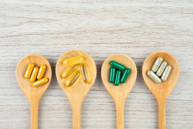 Herbal alternative medicine in capsules on wooden table with copy space for medical background