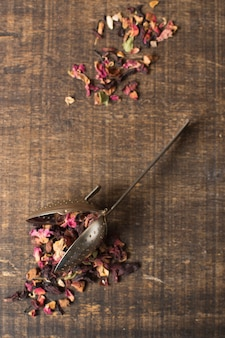 Herbal aroma tea dry petals with strainer on wooden textured backdrop