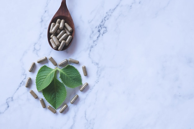 Herbal capsule from herb nature on white marble  with herbals leaves and copy space, medicine and drug concept