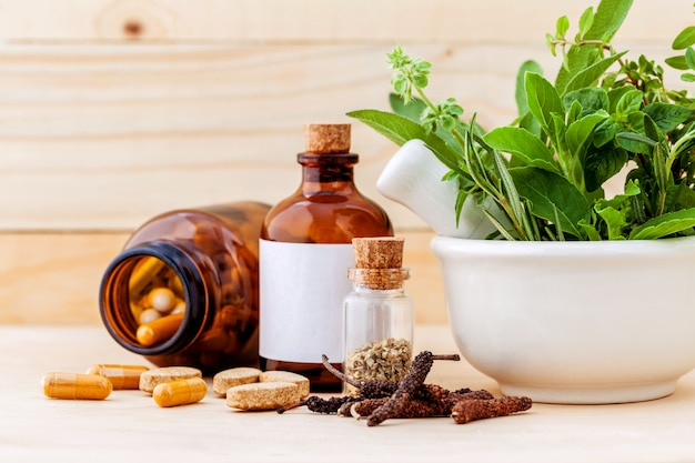 Herbal capsule on wooden background.