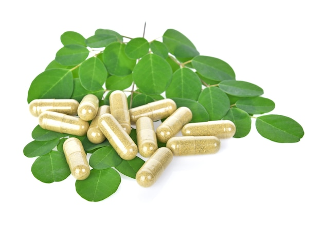 Herbal capsules with leaf  on white background