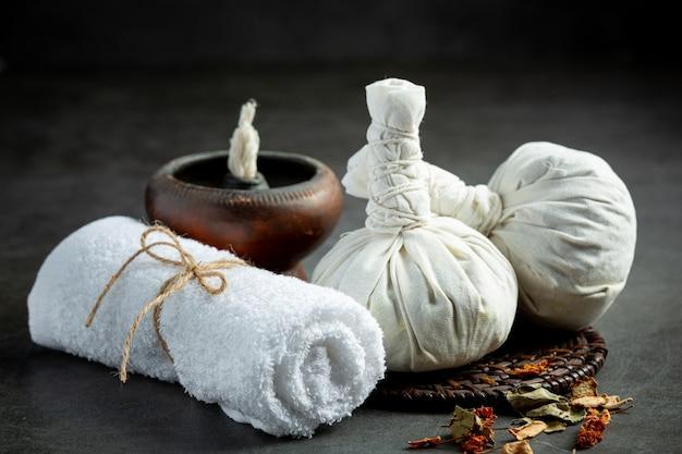Herbal compress and herbal spa treatment equipments put on dark floor