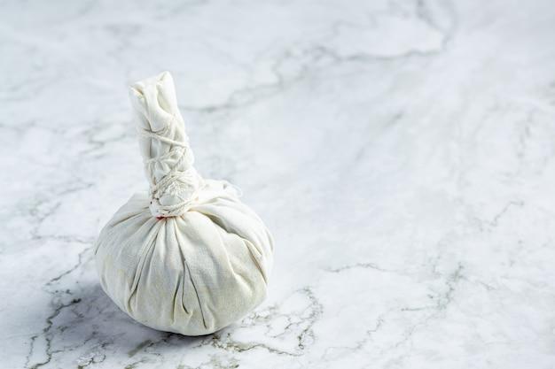 Impacco alle erbe messo sul pavimento di marmo bianco