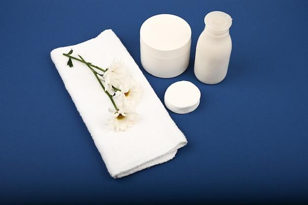 Травяные косметические флаконы с белым полотенцем сверху. крем баночки с натуральными ингредиентами. вид сверху