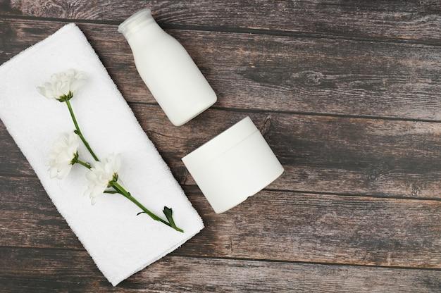 Травяные косметические флаконы с белым полотенцем сверху. крем баночки с натуральными ингредиентами.