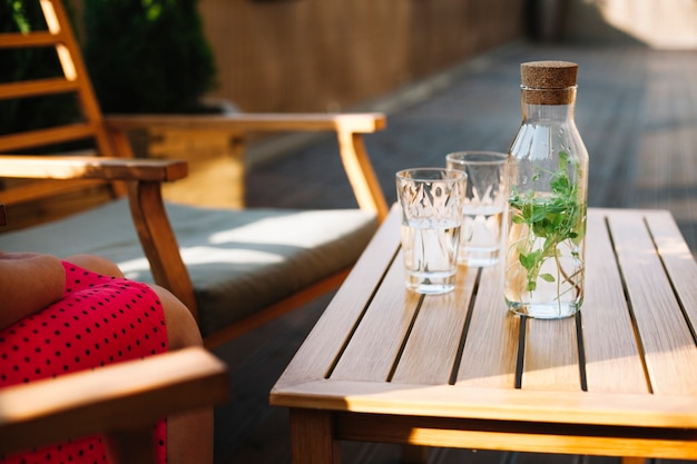 Herbal drink bottle with two glasses on wooden table