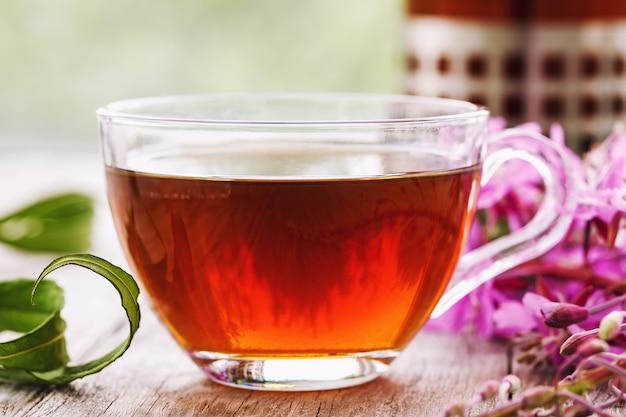 Травяной напиток ивантея в прозрачной чашке крупным планом на деревянном столе