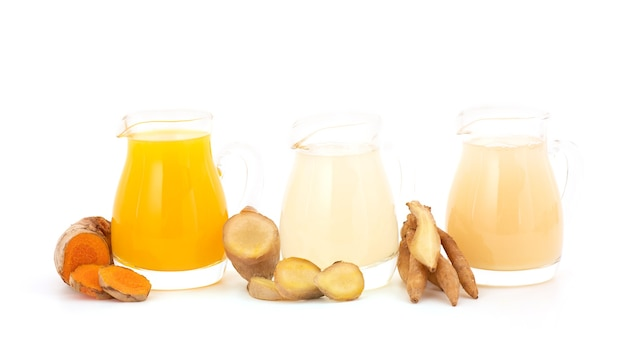 흰색 배경에 분리된 핑거루트, 생강, 심황 레몬, 꿀을 넣은 허브 음료.
