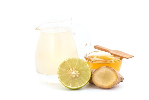 흰색 배경에 분리된 핑거루트, 레몬, 꿀을 넣은 허브 음료.