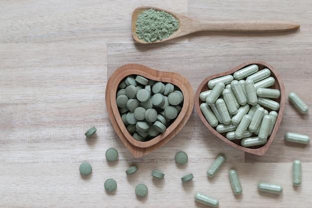 カプセルと粉末またはファタライチョン(andrographis paniculata)、木製の背景に木製のボウルにキツネノマゴ科、医療とヘルスケアの概念とハーブ抽出薬の錠剤の丸薬