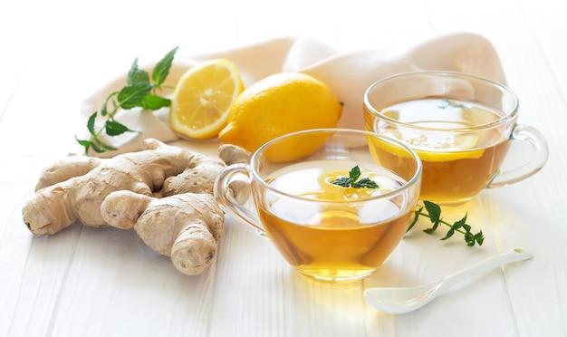 免疫力を高めるハーブジンジャーティー。健康的な温かい飲み物のクローズアップの2つのガラスのマグカップ