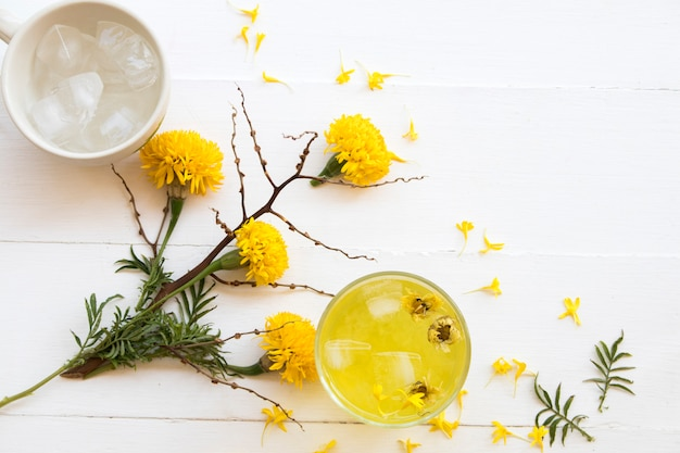 Herbal healthy drinks cold chrysanthemum flowers cocktail water beverage for health care with yellow flowers marigold