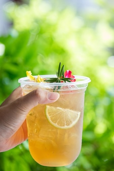 Herbal iced tea cocktail with edible flowers on wooden surface