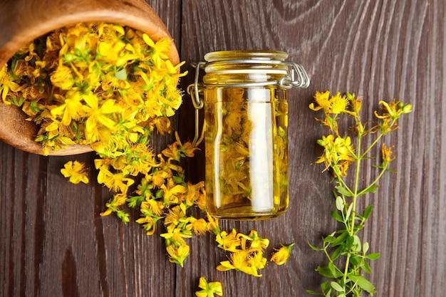 Hypericumperforatumまたはセントジョンズワートと木製のテーブルに生花をハーブで注入