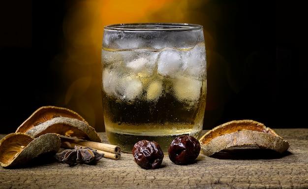 ぼけボケ背景の古い木製のテーブルに置かれた氷とドライフルーツと乾燥ハーブで満たされたガラスのハーブジュースとフルーツ。
