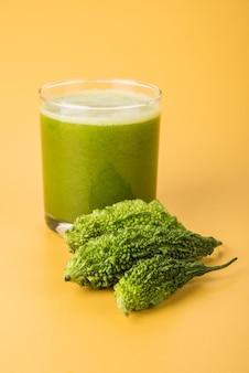 여주 또는 카렐라의 약초 주스는 당뇨병에 가장 좋은 천연 치료제입니다. 전체 쓴 멜론과 주스로 가득 찬 유리는 다채롭거나 나무 배경 위에 보관됩니다. 선택적 초점