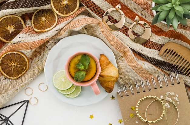 Herbal lemon tea with croissant and female accessories on tablecloth against white backdrop
