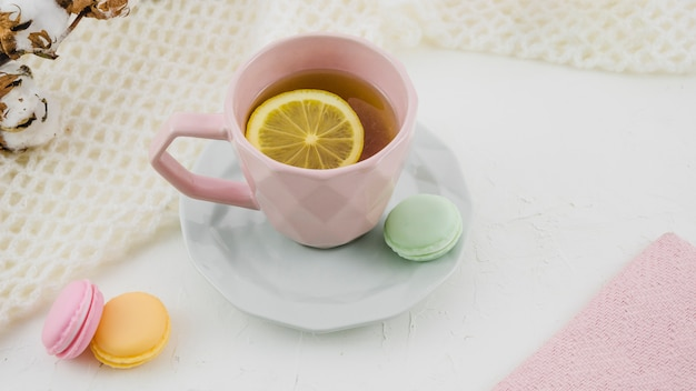 Herbal lemon tea with macaroons on white backdrop