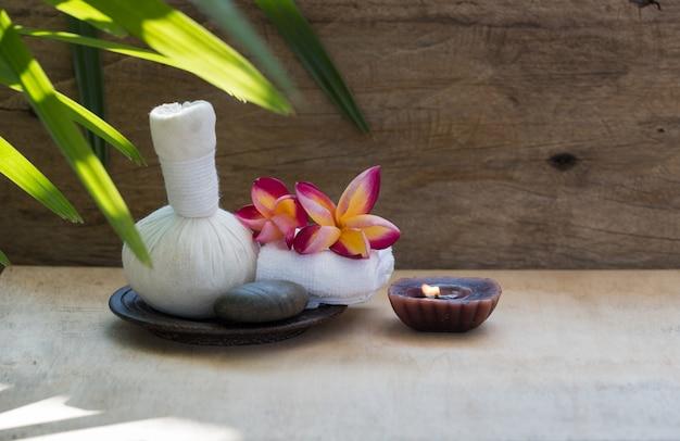 木製のテーブルにハーブマッサージボールとアロマテラピー製品