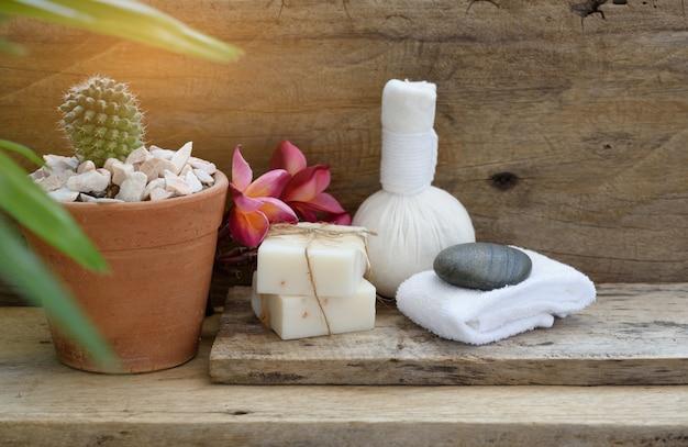 木製のテーブルにハーブマッサージボールとインディゴソープスパアロマセラピー製品