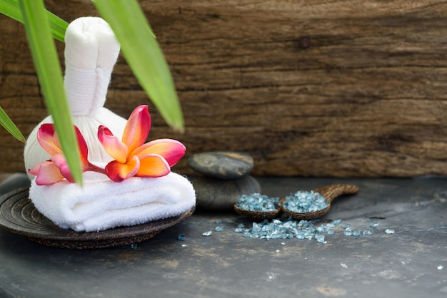 Herbal massage ball and indigo soap spa aromatherapy products on wooden table