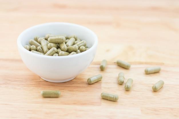 Herbal medicine capsules in ceramic cup,