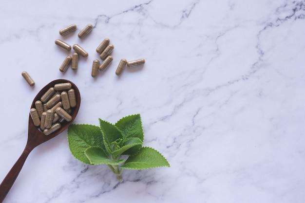 Herbal medicine in capsules on wood spoon