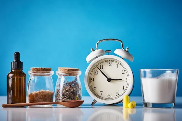 うつ病と不眠症の概念を治療するための漢方薬。目覚まし時計、薬草、青い背景のアロマテラピーオイル