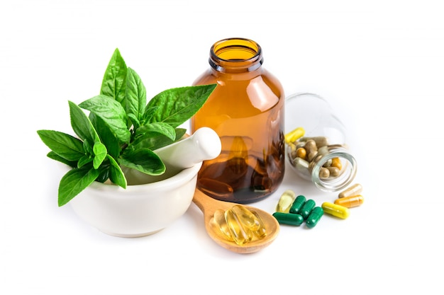 Herbal medicine from green leaf herb, pill, tablet, capsule, drug and vitamin in glass and wooden spoon