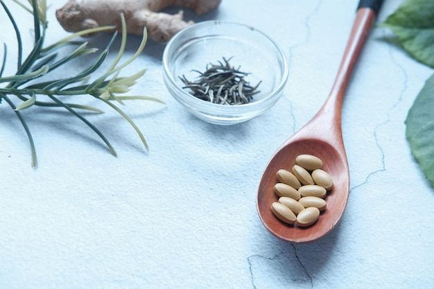 Herbal medicine on spoon and herbs on table