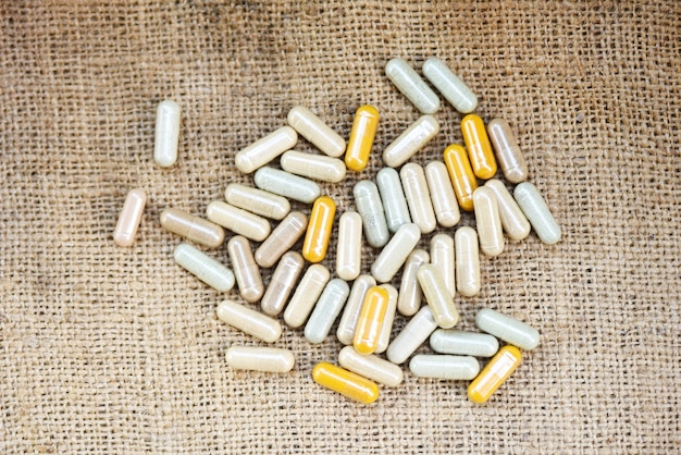 Herbal medicines - natural herb capsules on sack background , top view selective focus