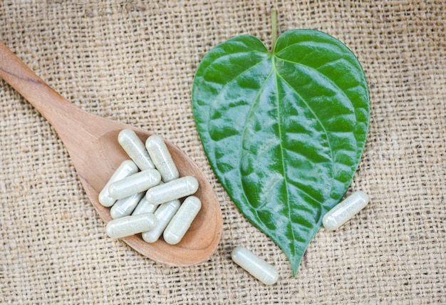 Herbal medicines / natural herb capsules on wooden spoon and green leaf on sack background