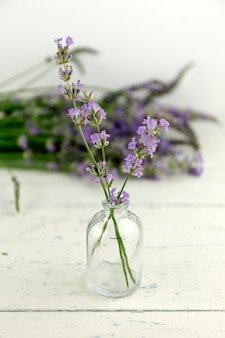 Herbal oil bottle and lavender flower on shaby wood