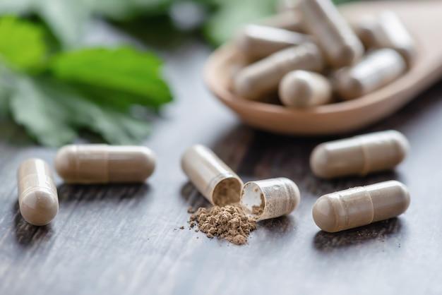 테이블과 나무 숟가락에 초본 알약 캡슐. 약물 및 허브 의료 건강 관리.