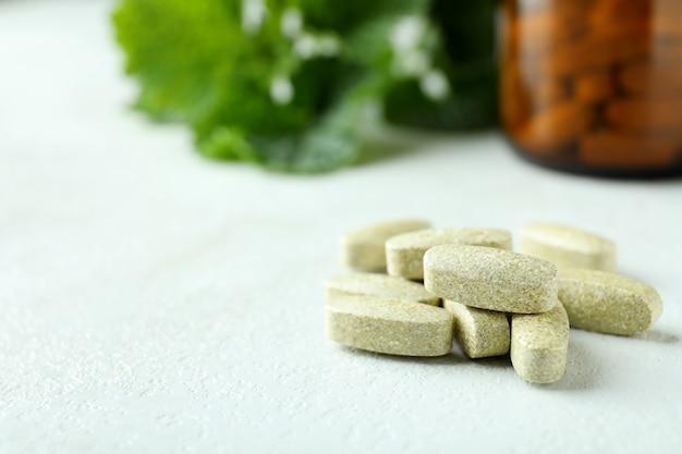 Травяные таблетки на белом текстурированном столе, крупным планом