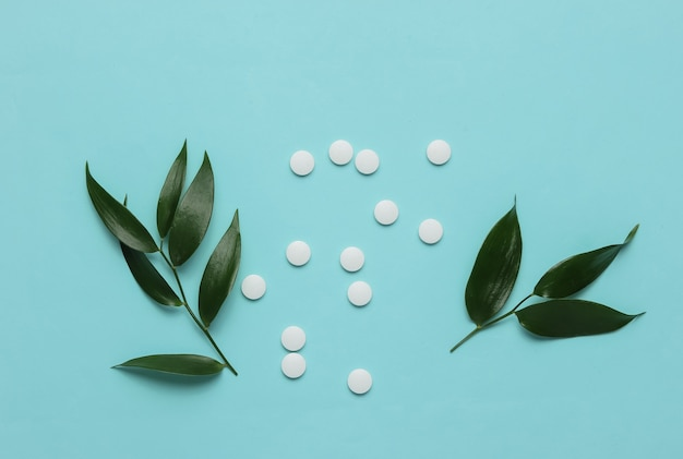 Herbal pills white pills with green leaves on a blue pastel background